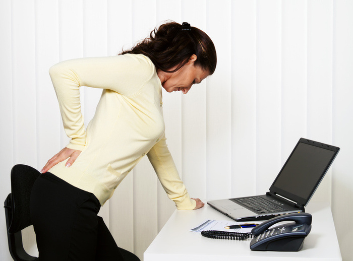 Woman with back pain of the intervertebral disc with office work at the desk.